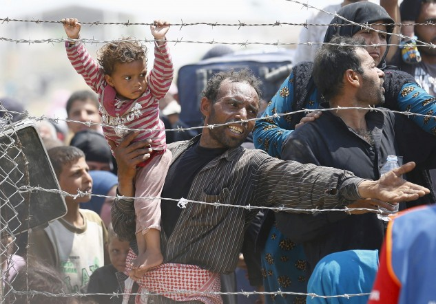 A Syrian refugee reacts as he waits behind border fences to cross into Turkey at Akcakale border gate in Sanliurfa province, Turkey, June 15, 2015. Photo by Umit Bektas/Reuters